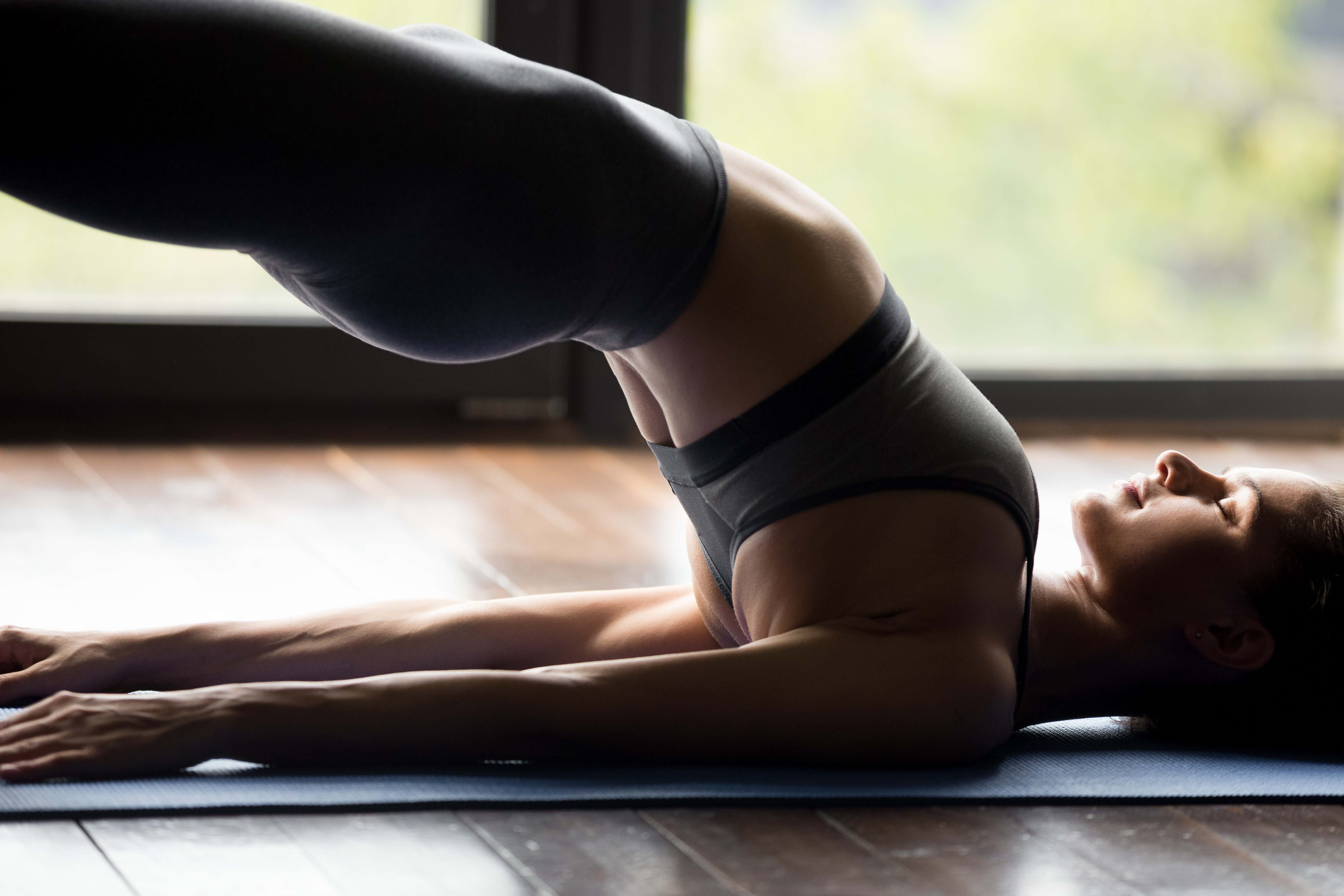 Young sporty woman practicing fitness or yoga, doing dvi pada pithasana exercise, Glute Bridge pose, working out wearing sportswear grey pants and top, indoor, body close up view, yoga studio concept