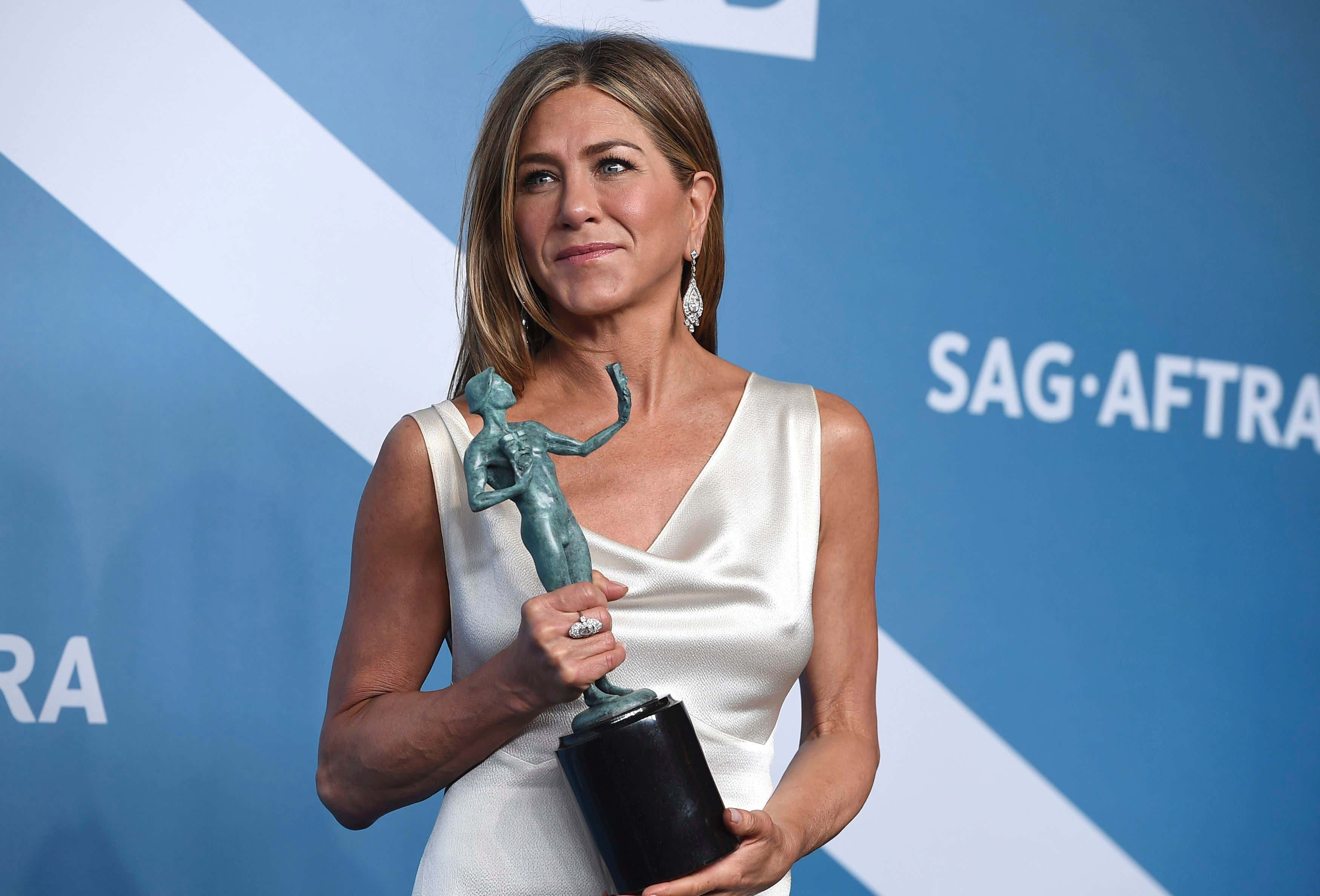 Jennifer Aniston poses in the press room with the award for outstanding performance by a female actor in a drama series for