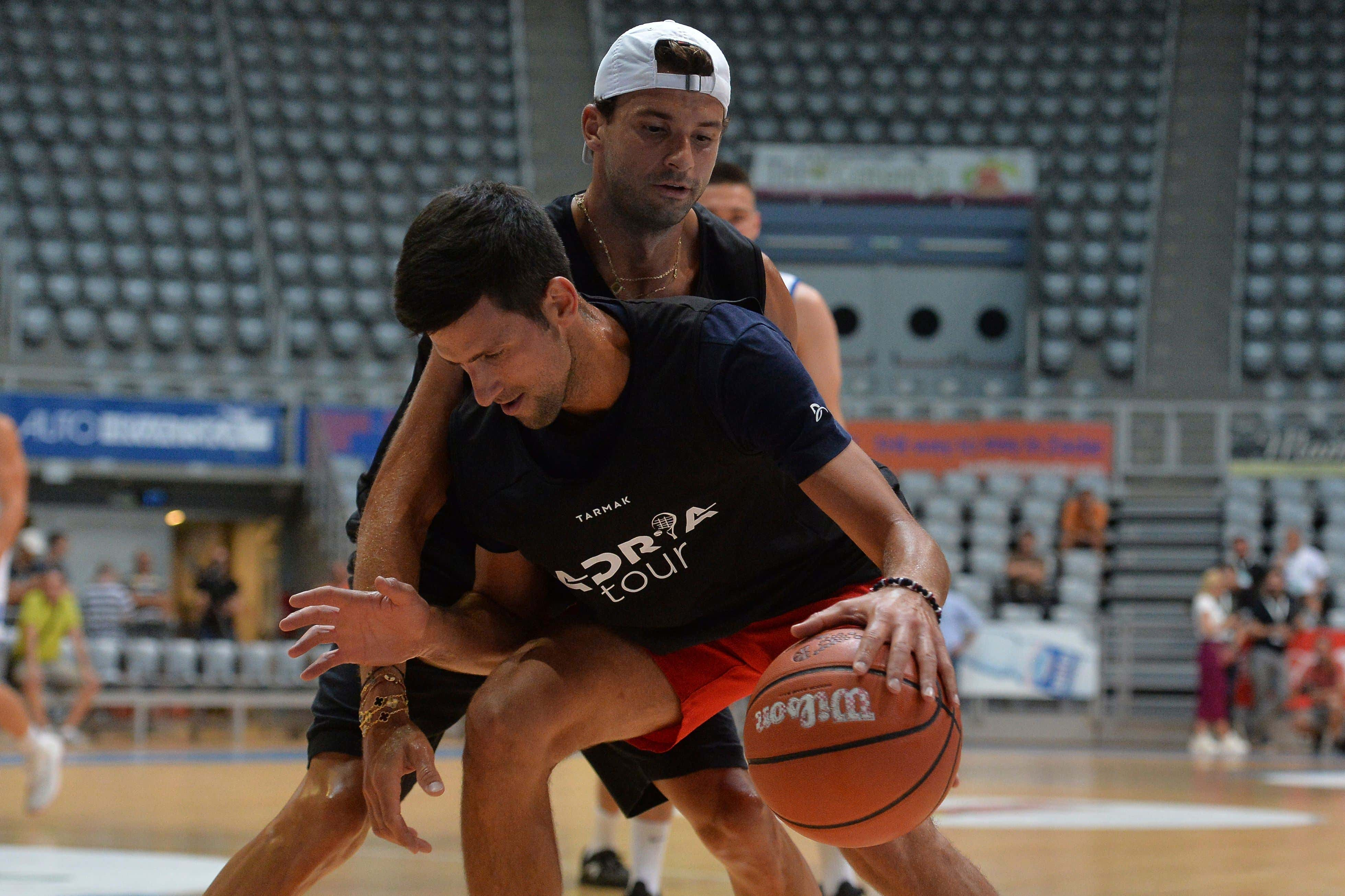 On, Bulgarian tennis player Grigor Dimitrov, rear, plays basketball with Serbia's Novak Djokovic in Zadar, Croatia. Dimitrovsays he has tested positive for COVID-19 and his announcement led to the cancellation of an exhibition event in Croatia where Novak Djokovic was scheduled to play on Sunday, June 21