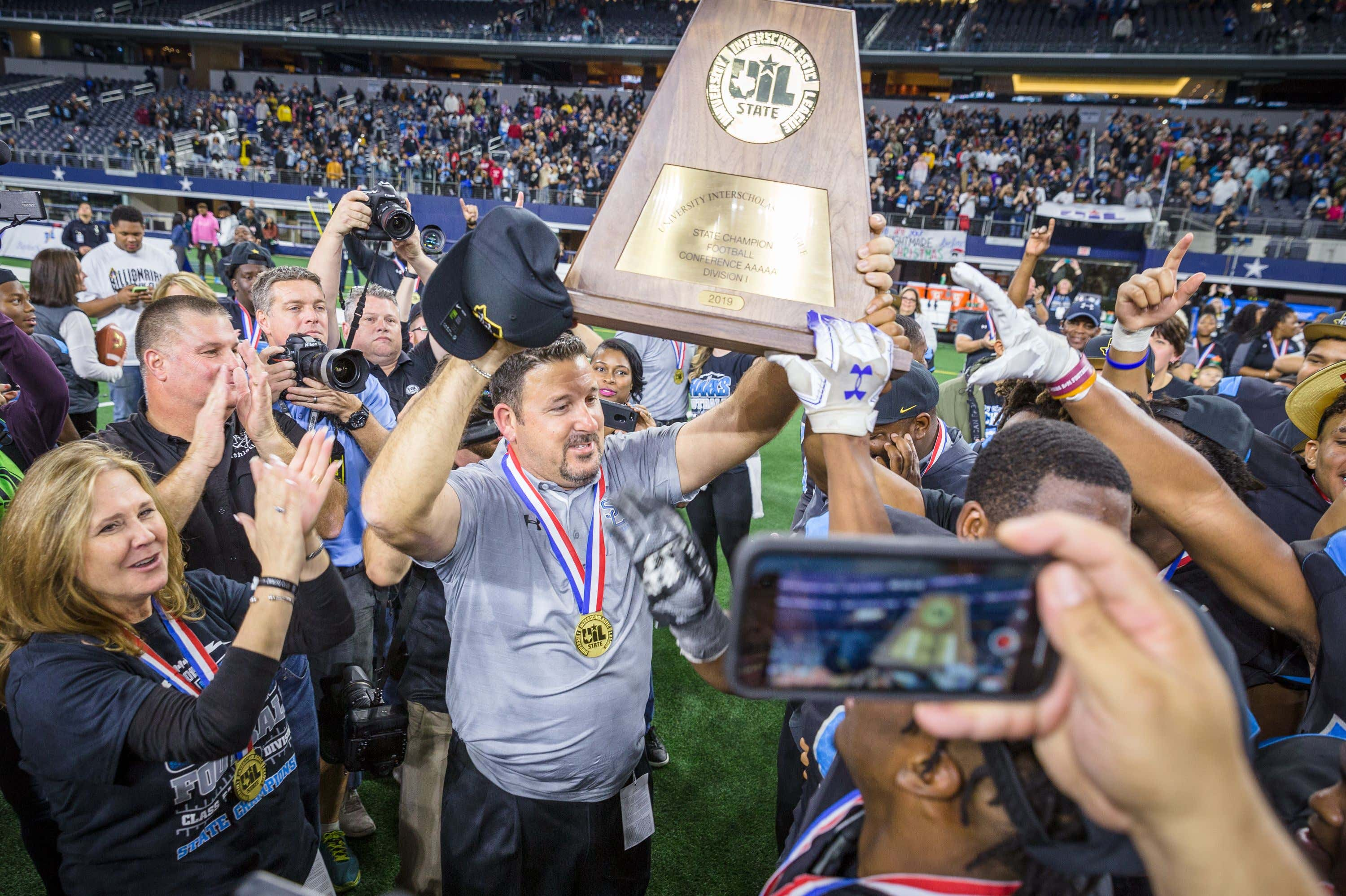 Alvin Shadow Creek Sharks head coach Brad Butler hoists the state championship trophy following the Texas University Interscholastic League (UIL) Class 5A Division 1 state championship game between the Denton Ryan Raiders and the Alvin Shadow Creek Sharks at AT&T Stadium in Arlington, Texas. Alvin Shadow Creek defeated Denton Ryan 28-22. Prentice C