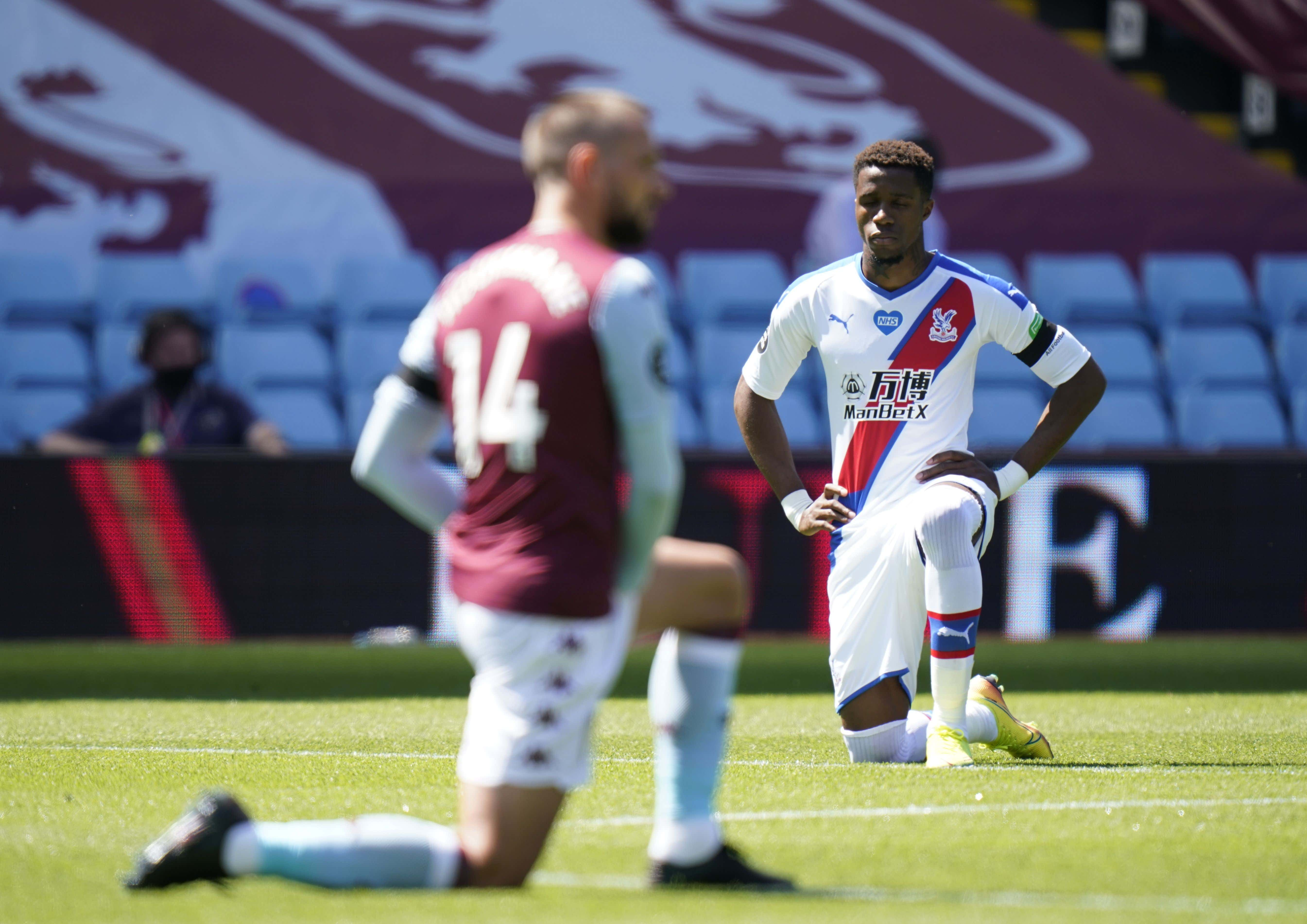 Wilfried Zaha (R) of Crystal Palace takes a knee in support of the Black Lives Matter campaign ahead of the English Premier League soccer match between Aston Villa and Crystal Palace in Birmingham, Britain, 12 July 2020.