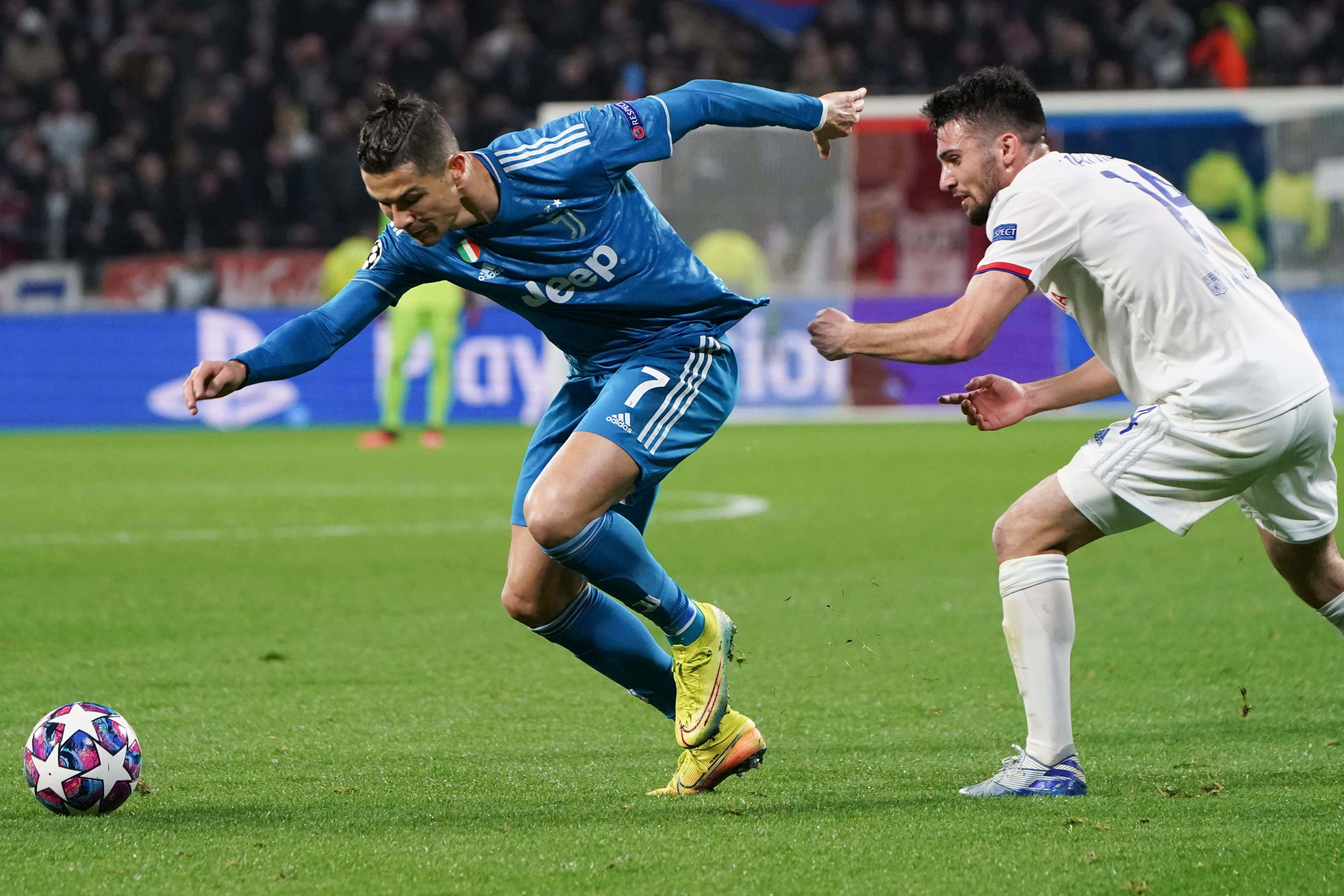 Lyon's Leo Dubois lets go of Juventus' Cristiano Ronaldo's shirt after restraining him during a round of sixteen, first leg, soccer match between Lyon and Juventus at the at the Lyon Olympic Stadium in Decines, outside Lyon, France