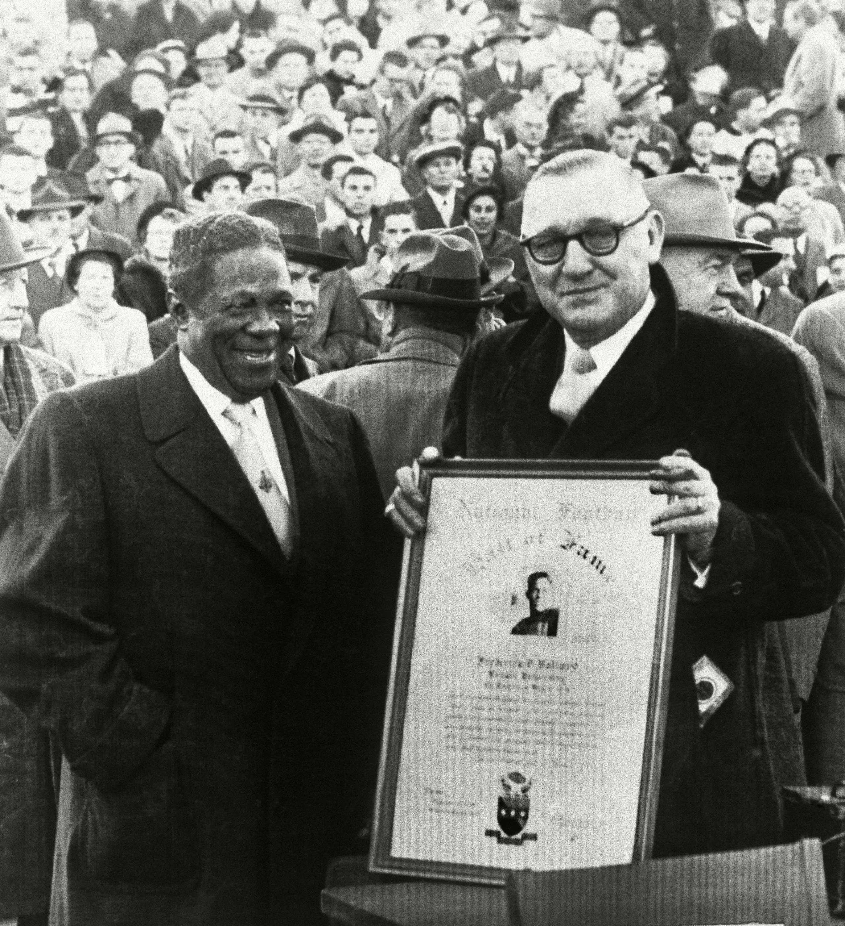 Fritz Pollard, left, all-time Brown Football great, receives a plaque as he is welcomed into the National Football Hall of Fame by Boston columnist Bill Cunningham during halftime ceremonies at the Brown-Springfield game in Providence, R.I