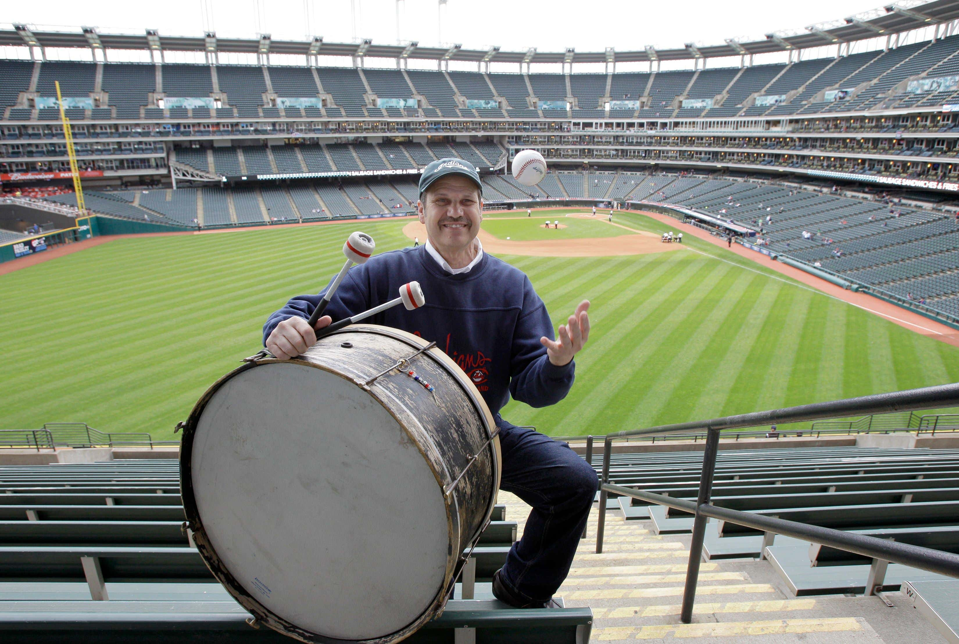 Cleveland Indians fan John Adams poses in his usual centerfield bleacher seat with his ever-present bass drum before a baseball game between the Indians and the Kansas City Royals in Cleveland. Adams, who will miss his first home opener since 1955 on Friday due to the coronavirus, has been keeping the beat for the Indians since 1973. AP Photo/Amy Sancetta, File