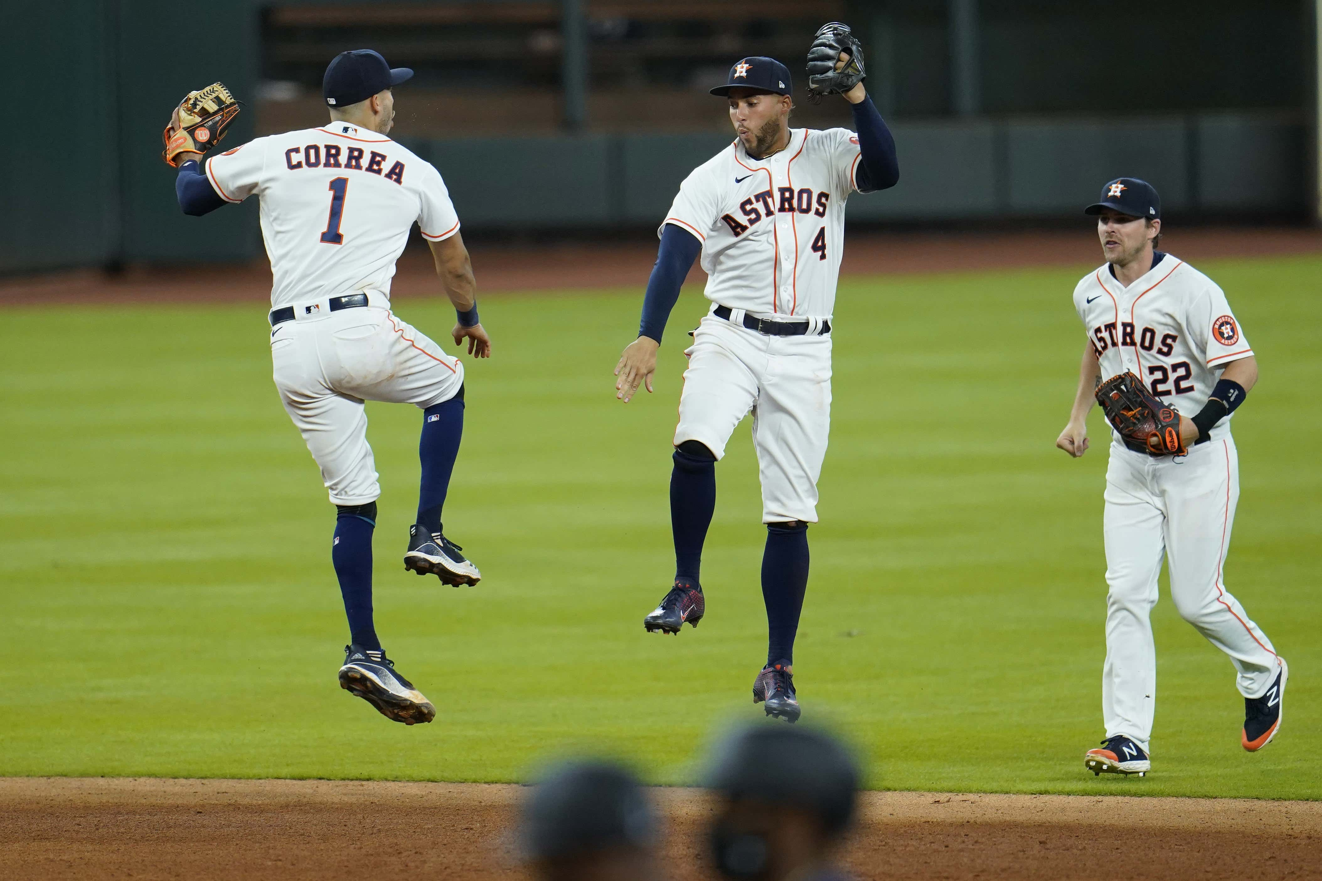 Houston Astros' Carlos Correa (1) and George Springer (4) celebrate after a baseball game against the Seattle Mariners, in Houston. The Astros won 7-2