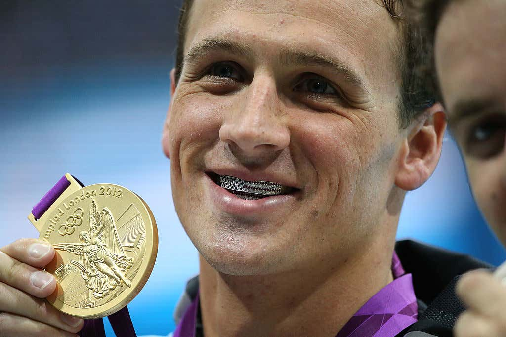Olympic gold medalist Ryan Lochte shows off his American flag grills and gold medal after winning t