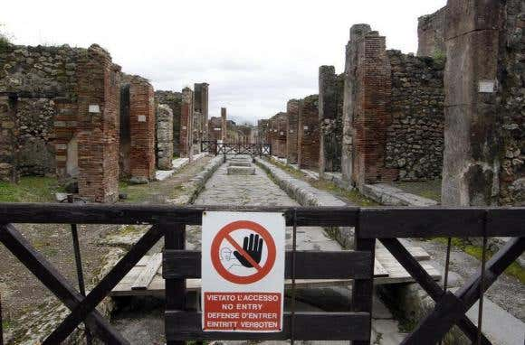 A sign hangs on a perimeter fence in the ancient Roman city Pompeii