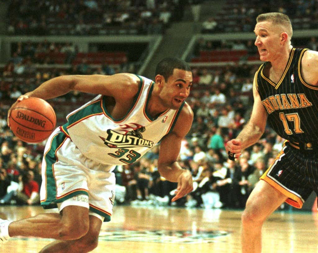 Detroit Pistons player Grant Hill (L) drives aroun