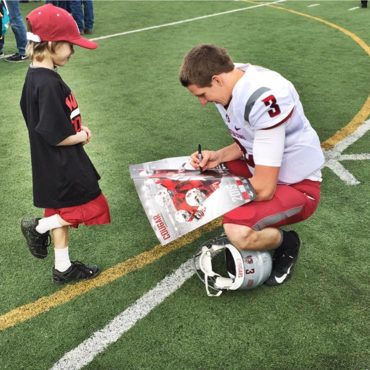 tyler-hilinski-autographing-a-poster-for-a-young-f