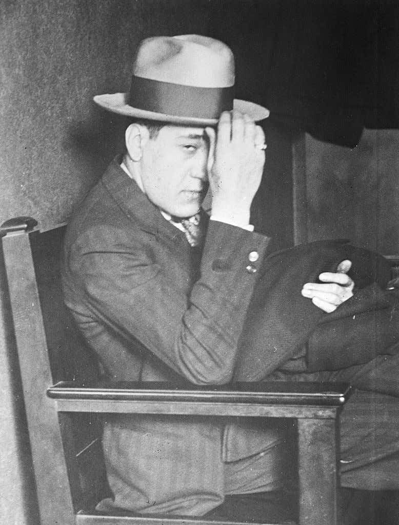 Tony Accardo Seated in Chair with Hand on Hat