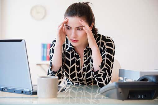 Caucasian businesswoman with headache using laptop