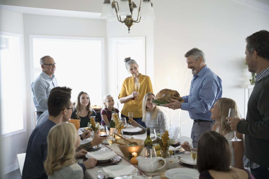 Man serving Thanksgiving turkey to family and friends at dinner table